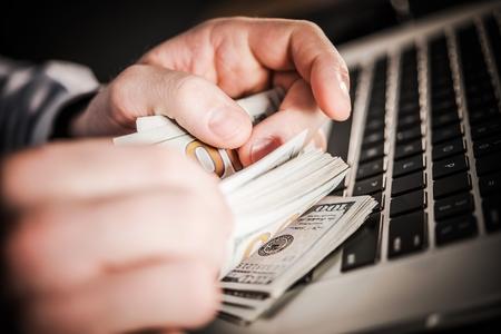 Making Money Online. Caucasian Businessman Counting Hard Earned Money. American Dollars. 版權商用圖片