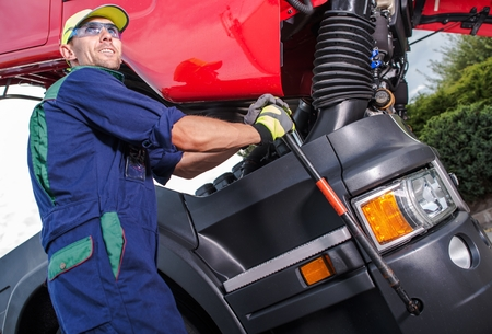 Semi Truck Maintenance by Professional Truck Mechanic. Caucasian Technician Preparing Truck Cabin For the Scheduled Engine Service. Фото со стока