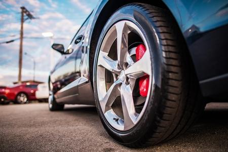 Samochód na parkingu. Zdjęcie zbliżenie koła ze stopu. Niższy poziom gruntu. Motyw dotyczący transportu i motoryzacji.