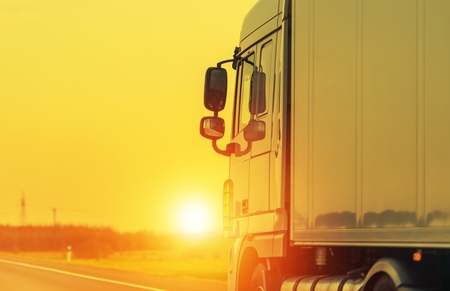 Road Shipping by Semi Truck. Heavy Load Long Haul Euro Transportation Theme. Sunset on the Highway. Stock Photo