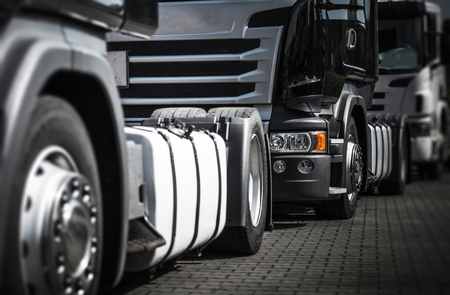 Euro Semi Trucks Staying in Traffic to the Storage Gate. Heavy Duty Transportation Theme. Stock Photo