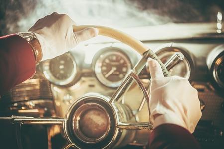 Classic Retro Car Driver. Men in White Gloves Driving His Vintage Vehicle. Steering Wheel Closeup. Reklamní fotografie