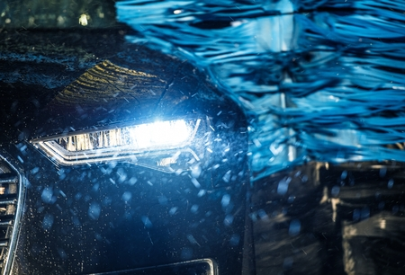 Modern Vehicle in the Automatic Brush Car Wash Closeup Photo.