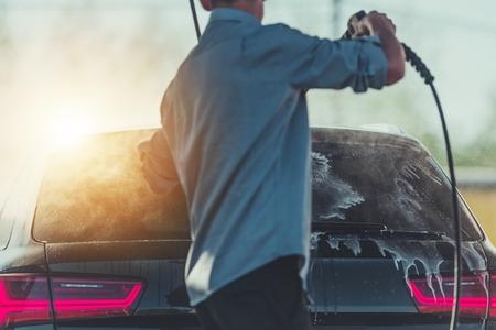 Man Washing His Car Using High Water Pressure Washer