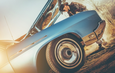 Cowboy and the Broken Classic Car on the American West Countryside Road. Reklamní fotografie