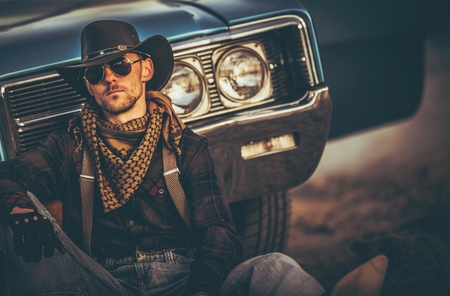 The Men of the Far West. Caucasian Western Wear Men in His 30s Relaxing in Front of His Classic Muscle Car. American West.
