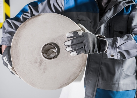 Worker with Large Roll of Industrial Use Paper. Closeup Photo
