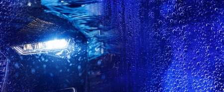 Modern Car Wash Banner Concept Background with Car in the Automatic Brush Washer. Deep Blue Color Grading.