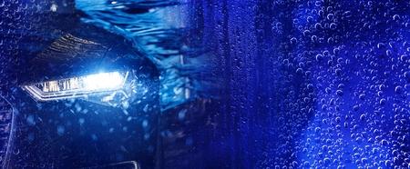 Moderner Autowasch-Banner-Konzept-Hintergrund mit Auto in der automatischen Bürstenwaschanlage. Tiefblaue Farbkorrektur.