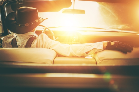 Going to the Sun Road. Western Wear Men in Cowboy Hat Driving Classic Convertible Car. American Dream Retro Style Concept. Reklamní fotografie