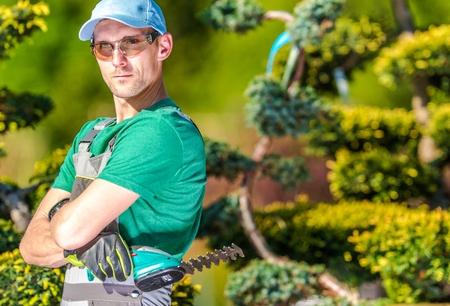 Professional Caucasian Gardener Portrait. Garden Worker with Compact Cordless Plants Trimmer. Reklamní fotografie