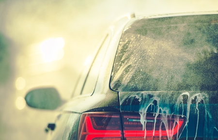 Cleaning Vehicle in the Car Wash. Closeup Photo. Auto Body Covered by Washing Detergent.