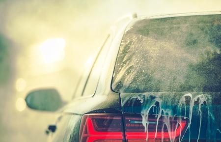 Vehículo de limpieza en el lavado de autos. Foto en primer plano. Carrocería cubierta por detergente de lavado.