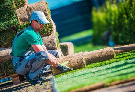 New Turf Grass Installation by Professional Gardener. Rolls of Grass on the Backyard.