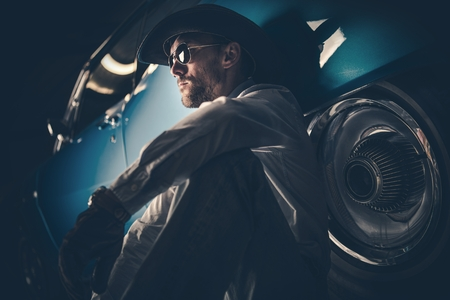 Portrait of the American Cowboy in His 30s Seating on the Side of His Classic Muscle Car.