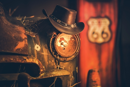 Route 66 Cowboys Concept. Cowboy Hat on the Rusty Classic Car with Broken Headlamp.