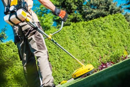Gas String Trimmer Work. Caucasian Gardener with Power Tool in the Garden. Reklamní fotografie