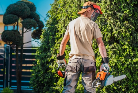 Men in the Garden. Caucasian Garden Worker with Power Tools Preparing For Spring Work. Gasoline Chain Saw and the Noise and Face Protectors.