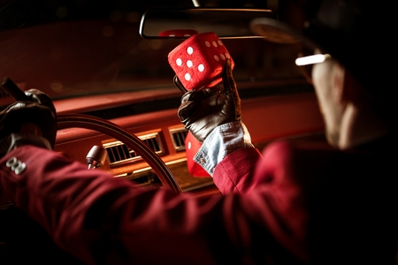 Casino Lucky Wish Concept. Casino Poker Player Talking to His Lucky Red Dice Inside the Classic Car.