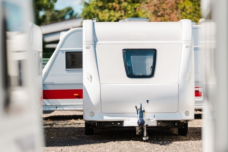 RV Travel Trailer Storage Parking. Modern Recreational Trailer with Front Window. Camping and Traveling Theme. Reklamní fotografie