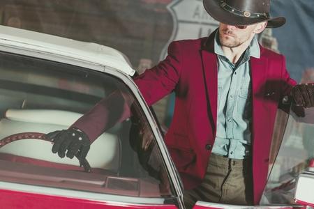 Western Wear Cowboy Driver. Caucasian Men and His Classic Vintage Car. American Transportation Theme.