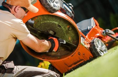 Caucasian Gardener in His 30s Checking Lawn Mower Blades.