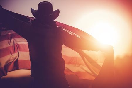 Independence Day Celebration. Western Wear Men in Cowboy Hat with United States of American Flag Celebrating 4th of July. Reklamní fotografie