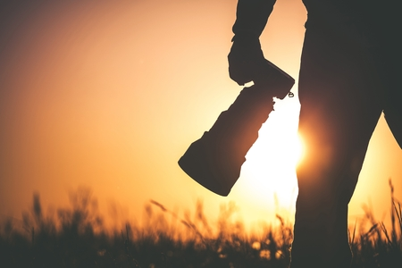 Safari Outdoor Photographer at Sunset. Silhouette of Men Keeping Digital Camera in Hand with Large Telephoto Lens For the Better Wildlife Closeups.