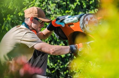 Caucasian Men Fixing Gasoline Lawn Mower in the Garden. Gardening Theme. Reklamní fotografie