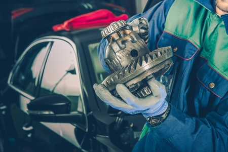 Caucasian Car Mechanic in His 30s with Part of Car Differential in Hands. Vehicle Service Theme. Reklamní fotografie