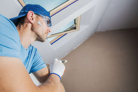 Room Painter Inspirations. Caucasian Man Refreshing His Dark Apartment by White Paint  Repainting. Reklamní fotografie
