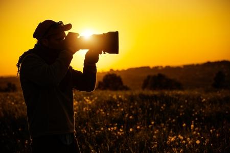 Fotógrafo apasionado al aire libre. Silueta escénica de la puesta del sol. Tema de fotografía digital moderna.