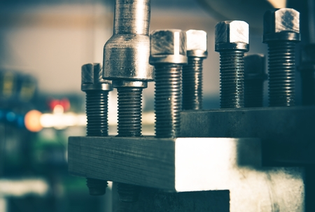 Industrial Grade Bolts Fasteners on the Lathe Machinery. Closeup Photo. Machine Adjuster.