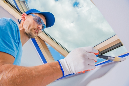 Room Painter in Action. Painting Apartment Interior with New Bright Paint. Construction Industry Theme. Caucasian Men in His 30s. Foto de archivo