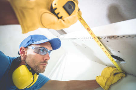 Building Precision and Accuracy. Caucasian Contractor in His 30s Measuring Drywall Ceiling Elements. Construction Theme.