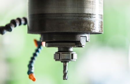 Industrial Heavy Duty Drilling Machine Closeup Photo. Drill Bit with Water Cooling Feature.
