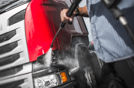 Trucker Washing His Semi Truck Using High Pressured Water Jet Cleaner. Stock Photo