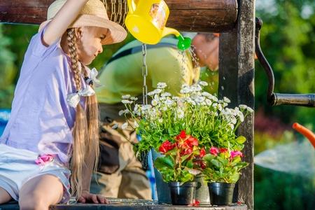Caucasian Girl Taking Care of Flowers. Watering Flowering Plants. Reklamní fotografie