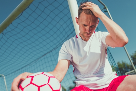 Heartbroken Caucasian Football Player in His 30s with the Ball on the Soccer Field.