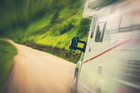 Motorhome Road Trip. Speeding Camper Van on the Mountain Road. Summer Travel Theme. Stock Photo - 104630045