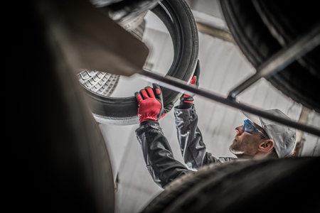 Vulcanizing Services Worker. Tires and Alloy Wheels Sales. Caucasian Vulcanization Technician Removing Tire From the Storage Shelf.