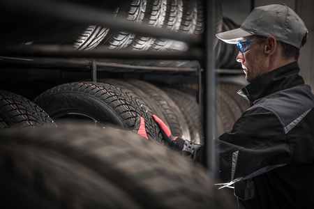 Choosing Right Car Tires For the Season. Vulcanization and Tire Sales Shop Caucasian Worker in His 30s. Automotive Theme. Reklamní fotografie