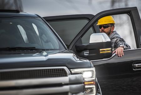 Hard Working Caucasian Men Wearing Yellow Helmet. Industrial Theme. Worker and His Corporate Pickup Truck.