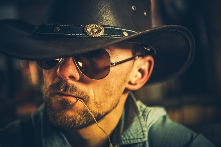 Caucasian Cowboy in His 30s with Grass Straw in His Mouth.. Portrait Photo.