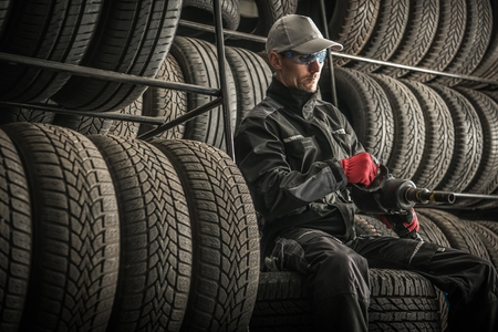 Car Tires Sales and Repair. Service Worker with Power Tool Between New and Used Tires. Automotive Theme. Seasonal Vehicle Tires Changes.