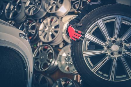 Picking New Alloy Wheels. Car Service Mechanic with Large Sport Utility Vehicle Wheel. Reklamní fotografie