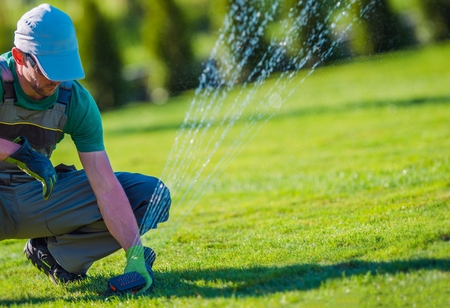 Lawn Sprinkler Installation by Professional Technician. Gardening and landscaping Theme.