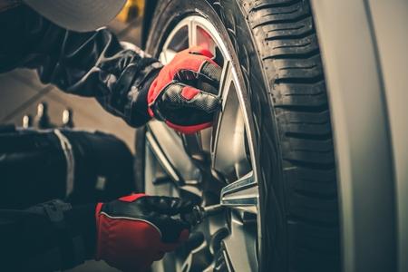 Seasonal Tires Replacement Automotive Photo Theme. Tire Sales Worker Finishing Change of Car Wheels. Closeup Photo. Reklamní fotografie