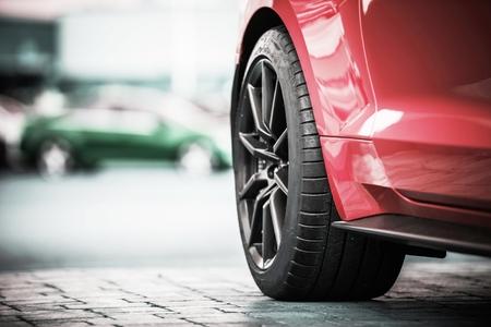 Modern Car Wheel. Red Sporty Car Alloy Wheel and Performance Tire Closeup Photo. Reklamní fotografie