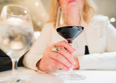 Woman with Glass of Wine in the Elegant Restaurant. Closeup Photo.